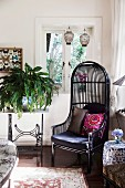 Elegant, black wicker chair in the corner of the living room next to a nostalgic sewing machine table with a green plant