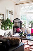 Black wicker chair next to nostalgic sewing machine table with green plants in living room with ethnic flair