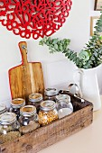 Wooden box with various storage jars and jug vase with leaf branch
