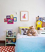 Girls room with pictures, cuddly toys and yellow table clock