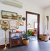 Anteroom with oriental floor lamp, shelf cabinet, pictures and house plants, view of the living room