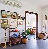 Vorraum mit orientalischer Stehleuchte, Regalschrank, Bildern und Zimmerpflanze, Blick ins Wohnzimmer