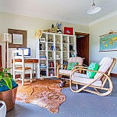 Comfortable armchairs, animal fur carpets, a workplace and a white, open shelf in the living room