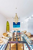 Rattan armchairs around long dining table with glass top, surfboard and picture with sea motif in background