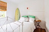 White metal bed with pillows, bedside table and surfboard in the bedroom