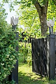 Open garden gate with artworks on posts and view into summery garden