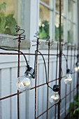 Simple fairy lights on rusty metal mesh against wooden façade