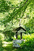 Vintage covered well with mossy wooden roof in garden