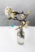 Frühlingsdeko: Papierherzen aufgehängt an Obstblütenzweig