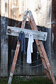 Clothes rack made from board and old shutter dogs on a ladder