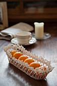 Fruit basket made from lace doily on wooden table