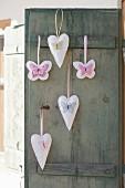 DIY-Anhänger mit aufgestickten Schmetterlingsmotiven an Vintage-Fensterladen
