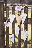 Hand-made pendants embroidered with butterflies hung on vintage picket fence