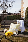 Cushion cover and tea towel embroidered with roses next to daffodils on garden bench