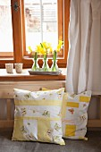 Hand-made patchwork cushions with butterfly motif on bench below daffodils on windowsill