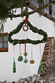 Hand made bird-cake balls hung from coathanger wrapped in fir sprigs