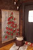 DIY-Adventskalender als Baummotiv mit aufgespannten, grünen Schnüren auf rustikaler Holzunterlage