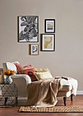 Cozy chaise longue with pillows and woolen blanket against beige wall with picture gallery