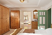 Wooden wardrobes in bedroom in renovated farmhouse with view into nursery