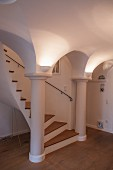 Winding staircase leading between huge columns and uplight sconces lighting arched ceiling