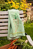 Tea towel embroidered with carrot motif on garden chair
