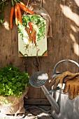 Hand-made key board with carrot motif on wooden door in garden