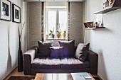 Scatter cushions on grey sofa in front of window in small room