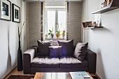 Graues Polstersofa mit Kissen vor Fenster in kleinem Zimmer