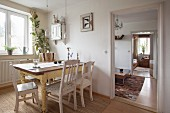 Rustic dining table, various chairs and window in dining area with view into living room