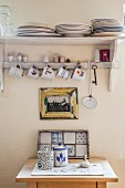 Beakers and tiled tray on small table below framed picture and vintage crockery shelf