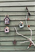Weathered birdhouse on wooden wall with white branch decorated nostalgically