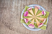 Pink carnations in ice-cream cones arranged in circles on green napkin on plate