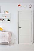 Wandteller über weisser Kassettentür, lackierte Antikkommode und String-Regal im Wohnbereich