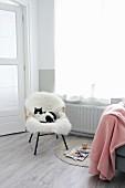 Rattanstuhl mit weißem Schaffell und Katze neben rosa Wolldecke und Zeitschriften