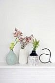 Retro arrangement of vases and flowers on white mantelpiece