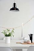 Ranunkelstrauss, Kerze und schwarze Trinkhalme auf weißem Esstisch vor rosa Girlande