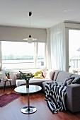 Gemütliche Couchecke mit Plaid vor sonnigem Fenster