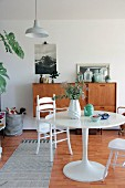 Round table and white high chair in front of retro sideboard