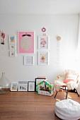 Korbstuhl mit hellem Schaffell und rosa Kissen neben verschiedenen Kinderzeichnungen und Häuschen mit Kakteen