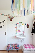 Colourful ribbons on lampshade in front of white sink in girl's bedroom