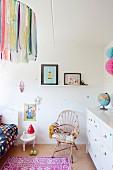 Mädchenzimmer mit Korbstuhl, weißem Schubladenschrank und Häkeldecke auf Bett