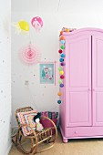 Pink wardrobe and cane rocking chair in pretty, girl's bedroom