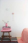Stack of pink cushions on rustic wooden stool on rag rug and necklace hanging from wall peg in bedroom
