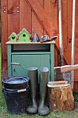 Cabinet and various gardening utensils outside wooden shed