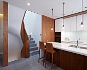 Modern kitchen with dark wooden doors and marble worksurface