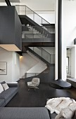 Staircase and suspended fireplace in double-height black-and-white interior