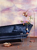 Sofa, side table and copper standard lamp against wall marbled in pink and purple