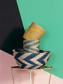 Bastkörbe mit farbigem Zick-Zack Muster vor Wand mit geometrischen Farbflächen