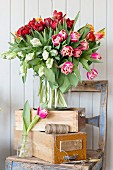 Opulent bouquet of tulips of various colours on stacked wooden crated on chair