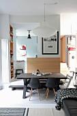 Rustikaler Holztisch mit Sitzbank und Klassikerstühlen in Wohnraum mit Podest